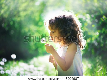 child has summer joy with dandelion - stock photo