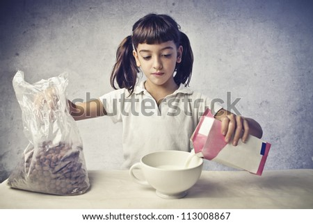 Child having a breakfast with cereals and milk - stock photo