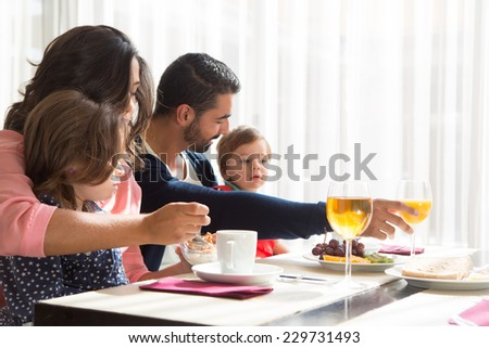 Child having breakfast with her mother and father - stock photo
