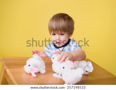 Child having fun and playing with wound up easter bunny toys - stock photo