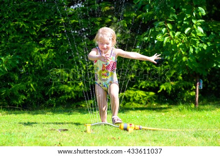 Child having fun outdoors in summer. Happy kid playing with garden sprinkler, running and jumping in swimming suit. Toddler girl gardening and watering grass - stock photo