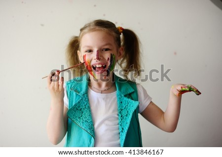 Child himself dirty in the paint and looks into the camera. Girl has fun and painting. Children's creativity. Art for baby. Dirty happy face child. Girl draws a brush face. - stock photo