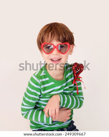 Child holding a valentine's day heart, laughing and smiling, happy, looking at camera. Success, great, excitement concept - stock photo