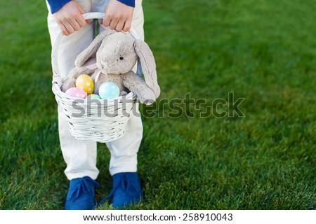 child holding basket with colorful easter eggs and bunny toy at spring time in the park - stock photo