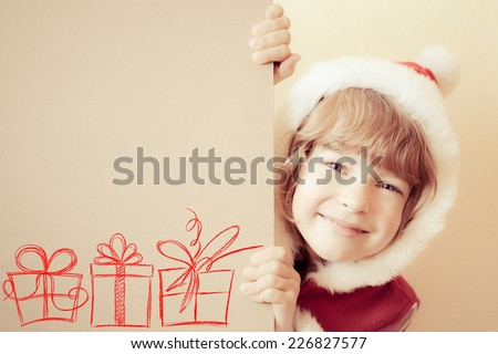 Child holding Christmas card blank with drawn gift boxes. Xmas holiday concept - stock photo