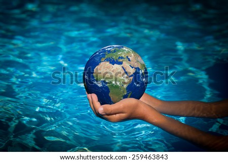 Child holding 3D planet in hands against blue water background. Earth day holiday concept. Elements of this image furnished by NASA - stock photo