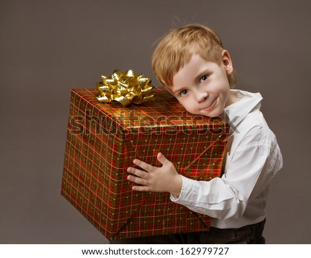 Child holding gift box, boy with big present.  - stock photo