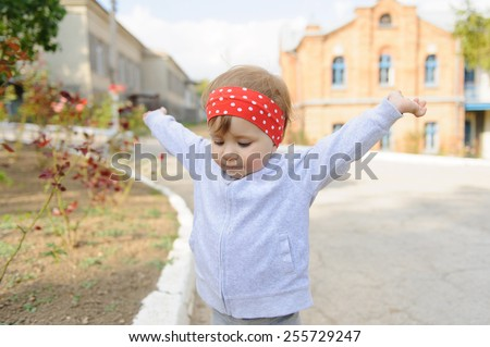 child holding her hands up in street - stock photo