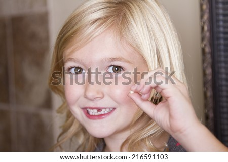 Child holding her missing front tooth - stock photo