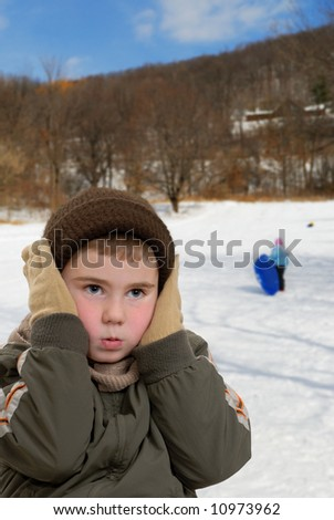 Child holding his ears against the cold - stock photo