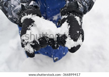 Child Holding Snow in Hands - stock photo
