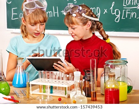 Child holding tablet pc in chemistry class. - stock photo