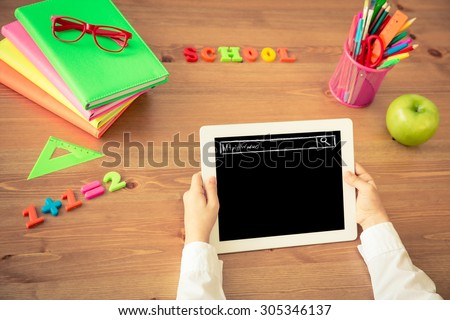 Child holding tablet PC in hands. School items on wooden desk in class. Education concept. Top view - stock photo