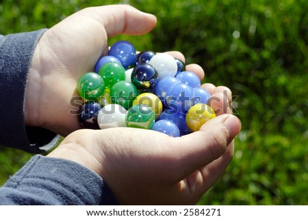 Child holding two hands full of marbles outdoors in the sunshine against a green grassy background - stock photo