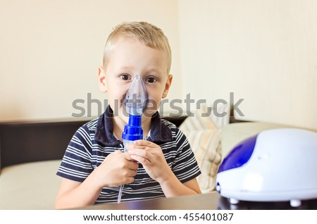 child holds a mask vapor inhaler. treatment of asthma. breathing through a steam nebulizer. concept of inhalation therapy apparatus.  - stock photo