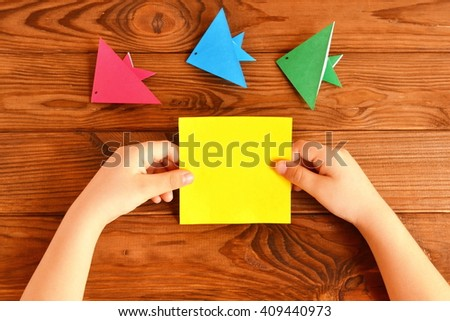 Child holds a paper square in his hands. Child making origami fish. Set of origami fish on a wooden table  - stock photo