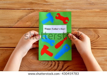 Child holds fathers day greeting card in his hands. Homemade fathers day greeting card idea. Preschool and kindergarten paper crafts. Handmade card idea. Happy father's day. Wooden table  - stock photo