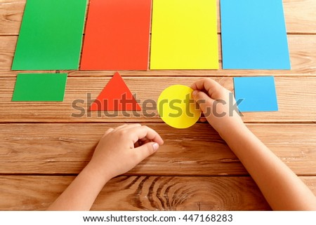 Child holds yellow cardboard circle in hands and puts on corresponding color card. Kid learns colors. Kit of colored cards for children of preschool age. Concept for learning in kindergarten, at home  - stock photo