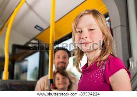Child in a bus; in the background presumably her father and sister to be seen - stock photo