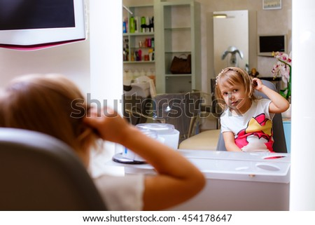 child in a chair at the barber - stock photo