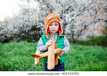 child in a helmet of the pilot with a toy airplane - stock photo