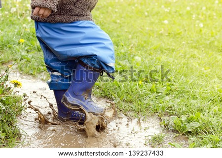 Child in boots jumping in muddy puddle after rain. - stock photo