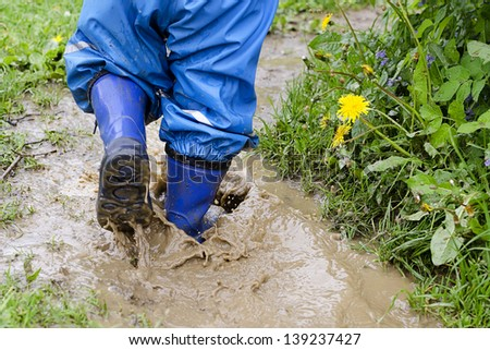 Child in boots walking and jumping in muddy puddle after rain. - stock photo