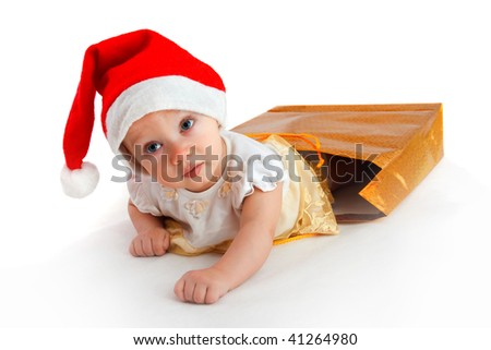 child in christmas hat crawl-out from the bag with presents - stock photo