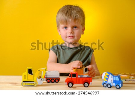 Child in kindergarten plays with wooden toys - stock photo