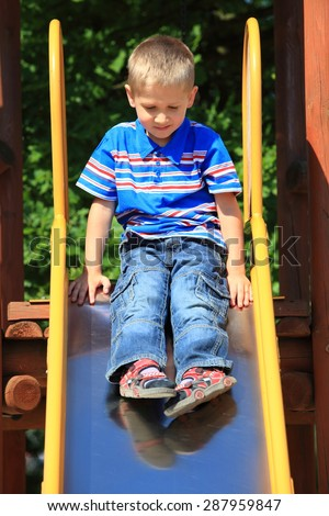 child in playground kid in action boy play on leisure equipment ready to slide down - stock photo
