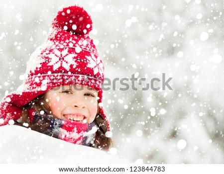 Child in red hat under snowfall - stock photo