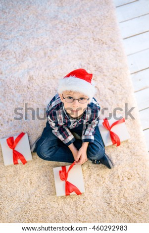 Child in Santa hat holding a christmas gift . - stock photo