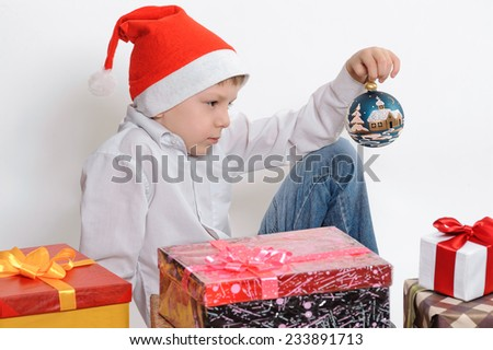 Child in Santa red hat holding Christmas ball in hands. Christmas concept. - stock photo