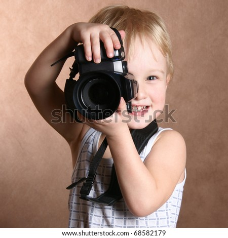 child in studio with professional camera - stock photo
