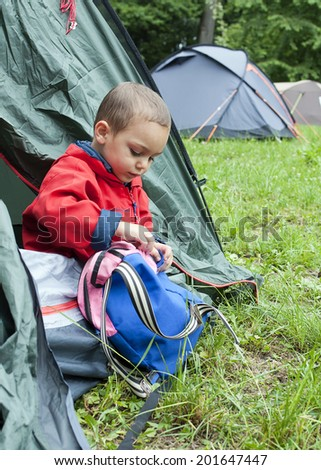 Child in tent at campsite on camping holiday, opening his bag. - stock photo