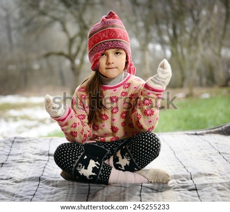 child in winter clothes in the lotus position. - stock photo