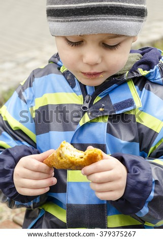 Child in winter hat eating bread roll or pastry  at street or park, aid or poverty concept. - stock photo