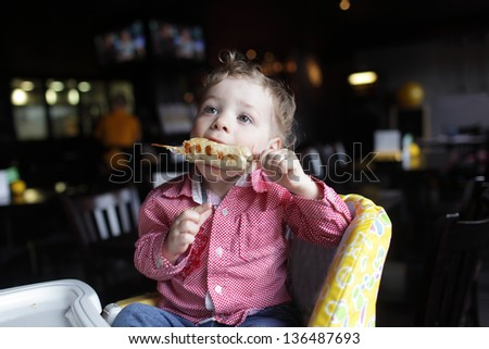 Child is eating kebab in a high chair at a restaurant - stock photo