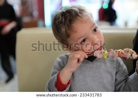 Child is eating kebab in the restaurant - stock photo