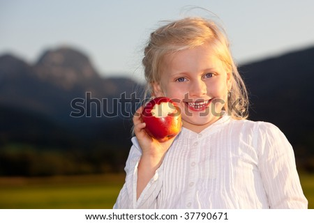 Child is holding a red apple and close to make a bite. Mountain in background - stock photo
