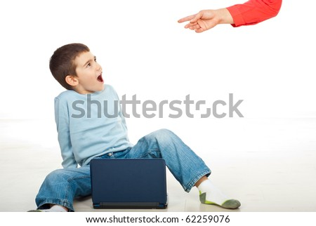 Child is not allowed to use laptop but is surprised by his mother using it and she arguing him - stock photo
