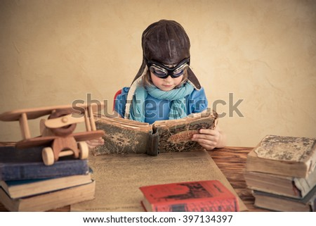 Child is pretending to be a pilot. Kid playing at home. Travel, freedom and imagination concept - stock photo