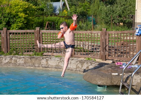 child jumps into the pool with water - stock photo