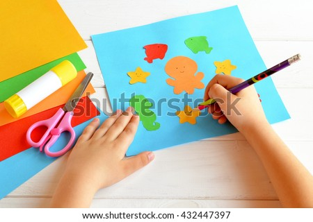 Child keeps a pencil in hand and draws. Scissors, glue stick, colorful paper, children applique. Cute paper sea animals. Kids skills. Crafts project idea. Kindergarten paper and glue crafts activity  - stock photo