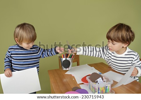 Child, kid engaged in arts and crafts activity, sharing and playing nice together - stock photo