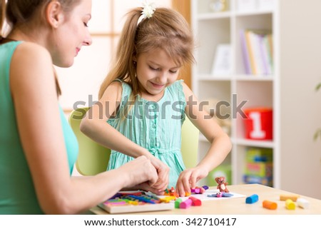 child kid girl and woman play colorful clay toy at nursery or kindergarten - stock photo