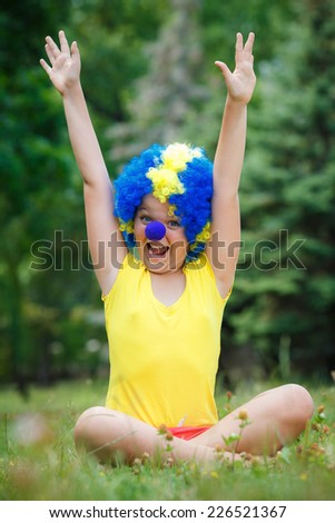 child kid girl with party clown blue wig funny happy open arms expression and garlands  in the park - stock photo
