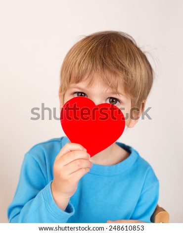 Child, kid, holding up a valentine's day paper heart,  - stock photo