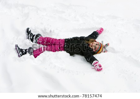 child laying down in the snow - stock photo