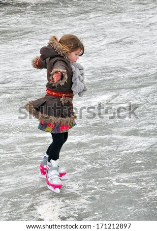 child learning to ice skate - stock photo